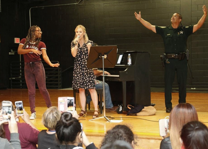 In this Sunday, Sept. 10, 2017, photo provided by Kristen Bell, the actress sings to evacuees taking refuge from Hurricane Irma at a shelter at the Meadow Woods Middle School in Orlando, Fla. Bell rode out the storm in Orlando, where she is filming a movie. (Kristen Bell via AP)