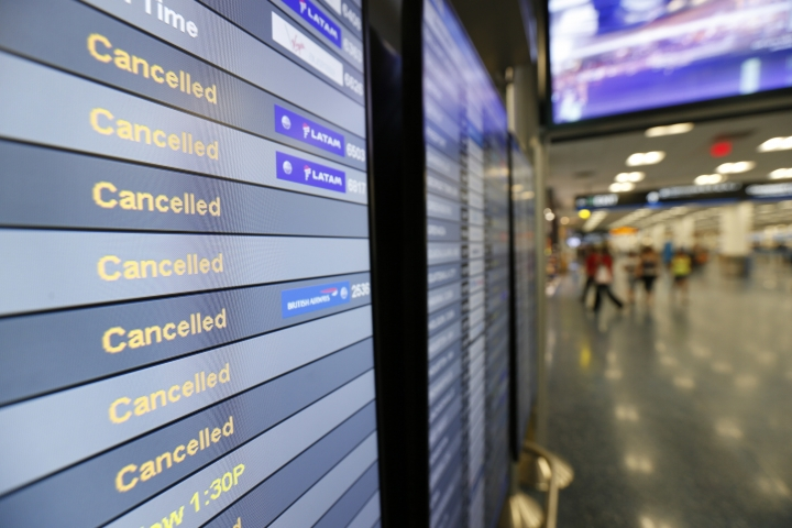 FILE - This Friday, Sept. 8, 2017, file photo, shows a monitor listing canceled flights at Miami International Airport in Miami. As of Monday, Sept. 11, 2017, airlines have canceled more flights as air travel in Florida remains grounded and Irma spins farther north. High winds have caused Delta and American to cancel many flights in Atlanta and Charlotte, N.C. Airlines hope to resume Miami flights Tuesday. (AP Photo/Wilfredo Lee, File)