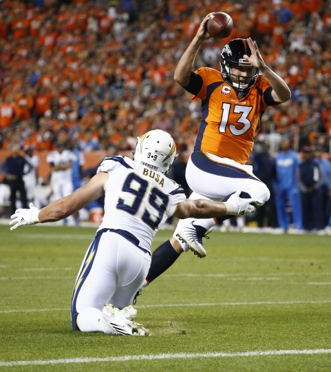 Denver Broncos quarterback Trevor Siemian (13) eludes Los Angeles Chargers defensive end Joey Bosa (99) for a touchdown run during the first half of an NFL football game, Monday, Sept. 11, 2017, in Denver. (AP Photo/Jack Dempsey)