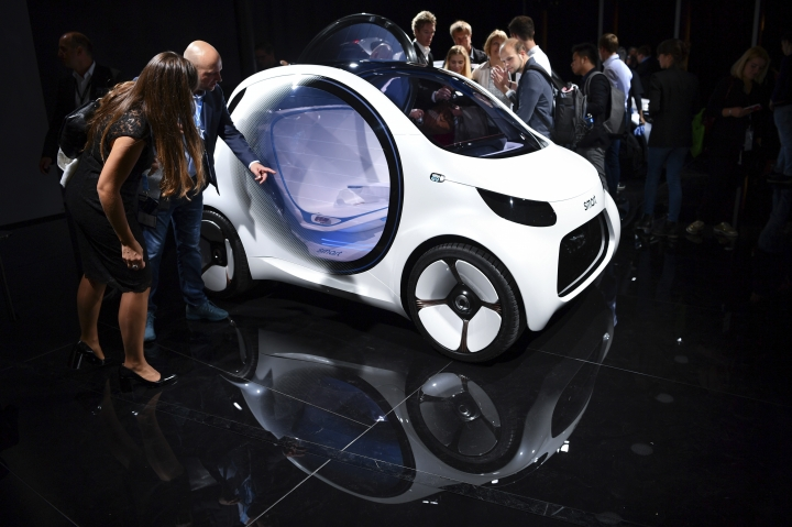 Visitors stand next to a Smart 'Vision EQ' on the first press day of the Frankfurt International Motor Show IAA in Frankfurt, Germany, Tuesday, Sept. 12, 2017. (Uwe Anspach/dpa via AP)