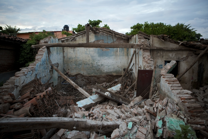 A cat lies amidst the remains of Peregrina Vera's home, destroyed in Thursday's magnitude 8.1 earthquake, in Juchitan, Oaxaca state, Mexico, Monday, Sept. 11, 2017. Vera, a Oaxacan muxe, said the cat had moved her four newborn kittens into the house just two days before the quake collapsed the building, burying them in rubble. Ever since, the cat has been sleeping atop the debris in the spot where she lost her kittens. (AP Photo/Rebecca Blackwell)