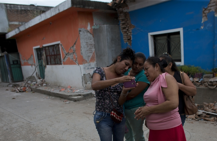 """Peregrina Vera, a Oaxacan muxe, shows pictures of homes destroyed and damaged in Thursday's magnitude 8.1 earthquake, to friends as they discuss their experiences of the massive quake in Juchitan, Oaxaca state, Mexico, Monday, Sept. 11, 2017. """"It started slow, slow and we were thinking that was it,"""" Vera said. Then there was crashing, darkness. """"People yelling. Everyone crying."""" (AP Photo/Rebecca Blackwell)"""