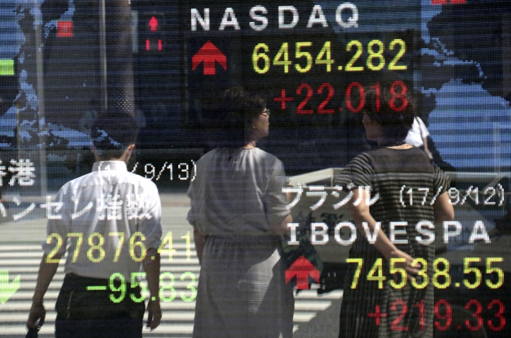 People are reflected on an electronic stock indicator of a securities firm in Tokyo, Wednesday, Sept. 13, 2017. Most Asian stock markets were higher Wednesday after U.S. shares rose on encouraging jobs data while worries about North Korea and twin hurricane disasters eased. (AP Photo/Shizuo Kambayashi)