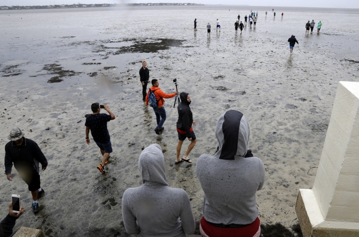 FILE - This Sept. 10, 2017, file photo shows people walking on Old Tampa Bay, in Tampa, Fla. Hurricane Irma's devastating storm surge came with weird twists that scientists attribute to the storm's girth, path and some geographic quirks. They can explain why the highest water levels observed from Irma were in faraway corners, while places closer to the eye experienced a rare reverse surge. (AP Photo/Chris O'Meara, File)