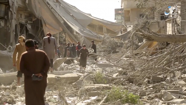 FILE - This undated file frame grab from video posted online Monday, May 29, 2017 by the Aamaq News Agency, a media arm of the Islamic State group, shows people inspecting damage from airstrikes and artillery shelling in the northern city of Raqqa, Syria. Hundreds of thousands of amateur videos uploaded by Syrian activists as well as militants to YouTube documenting every heartbeat of the Syrian war have been removed as the tech giant applies new technology to rein in violent content on the internet, causing a panic among the activists who fear the loss of evidence of human rights violations. (Aamaq News Agency via AP, File)
