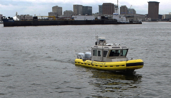 """In this Tuesday, Aug. 15, 2017 photo, a boat capable of autonomous navigation makes its way around Boston Harbor. The experimental workboat spent this summer dodging tall ships and tankers, outfitted with sensors and self-navigating software and emblazoned with the words """"UNMANNED VESSEL"""" across its aluminum hull. (AP Photo/Steven Senne)"""