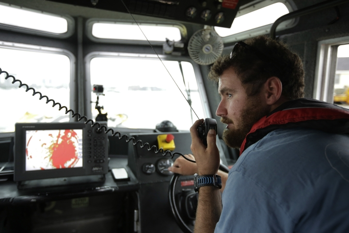 In this Tuesday, Aug. 15, 2017 photo, Jeff Gawrys, marine technician for Boston startup Sea Machines Robotics, prepares to disengage the navigation of a boat and switch the vessel over to fully autonomous control in Boston Harbor. Spurred on by the car industry's race to build driverless vehicles, maritime companies are taking advantage of technological breakthroughs and broader public acceptance of artificial intelligence to design tugboats, ferries and cargo vessels that won't need captains or crews, at least not on board. (AP Photo/Steven Senne)
