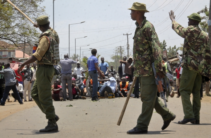 Kenyan police prevent opposition protesters who had blocked roads and thrown rocks from trying to storm a hotel in Kisumu, western Kenya Wednesday, Sept. 13, 2017. A Kenya police official says riots broke out in the opposition stronghold of Kisumu city after a rumor spread about alleged efforts to rig next month's presidential election. (AP Photo/Amos Aura)