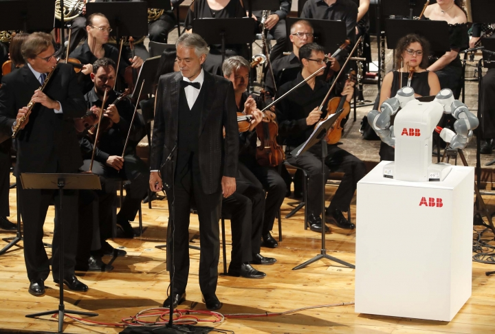 "Italian tenor Andrea Bocelli, center, performs Giuseppe Verdi's opera ""La Donna e' Mobile"", on stage next to the robot YuMi conducting the Lucca Philharmonic Orchestra, at the Verdi Theater, in Pisa, Italy, Tuesday, Sept. 12, 2017. A world famous tenor, a celebrated orchestra and a robot conductor were the highlight of Pisa's inaugural International Robotics Festival which runs from Sept. 7 to Sept. 13. (International Robotics Festival Pisa via AP)"