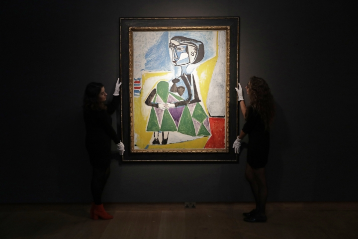 "Christie's auction house staff pose for photographs with the 1954 Pablo Picasso painting ""Femme accroupie (Jacqueline)"", a portrait of Jaqueline Roque, Picasso's final great muse and eventually his second wife, at their premises in London, Wednesday, Sept. 13, 2017. The painting is estimated to fetch between $20 and $30 million (16.7 and 25 million euro) in an Evening Sale of Impressionist and Modern Art on November 13 in New York. (AP Photo/Matt Dunham)"
