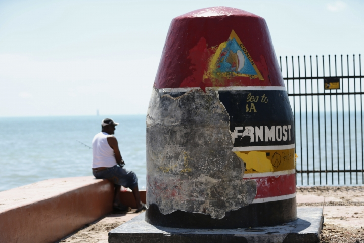 A man fishes next to the Southernmost Point Buoy damaged by Hurricane Irma, Wednesday, Sept. 13, 2017, in Key West of the Florida Keys. (AP Photo/Wilfredo Lee)