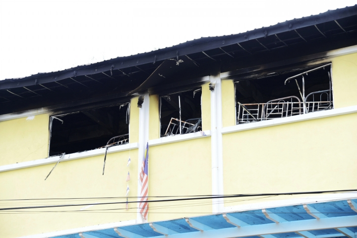 Burned windows of an Islamic religious school is seen after firefighters put out a fire on the outskirts of Kuala Lumpur Thursday, Sept. 14, 2017. The official said the fire started early Thursday at the top floor of the three-story building that is believed to be a dormitory. (AP Photo)