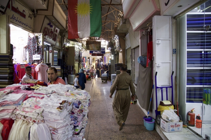 In this Thursday, Aug. 24, 2017 photo, a Kurdish man wearing traditional clothes passes under a Kurdish flag in Irbil's old bazaar, Iraq. Despite calls from Baghdad and the United States to postpone the vote, Iraq's semi-autonomous Kurdish region is pressing ahead with plans to hold a referendum on independence September 25. Some officials within Iraq's Kurdistan Regional Government describe the vote as a step in pursuit of self-determination, but the lead up to the planned referendum has highlighted the region's lingering divisions and economic deficiencies.(AP Photo/Balint Szlanko)
