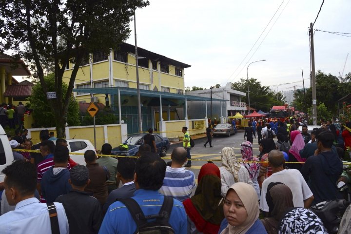 People gather outside an Islamic religious school which was cordoned off after the fire on the outskirts of Kuala Lumpur Thursday, Sept. 14, 2017. A fire department official in Malaysia said a fire at the Islamic religious school has killed people, mostly teenagers. (AP Photo)