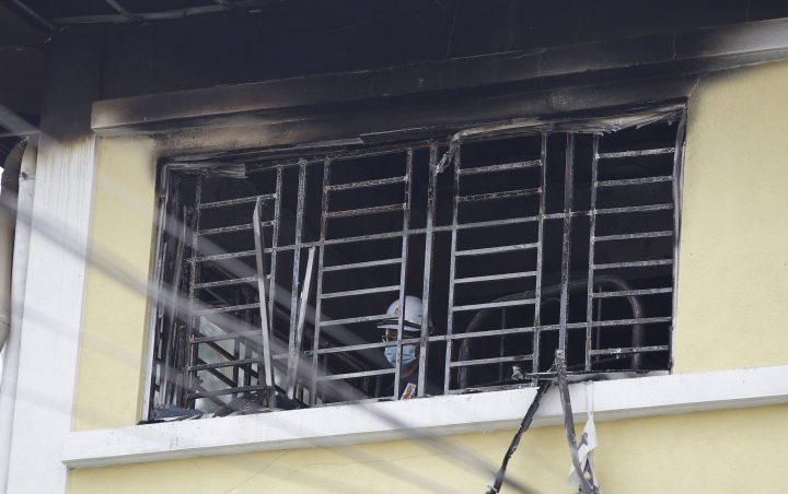 Forensic police officer investigates burnt windows at an Islamic religious school following a fire on the outskirts of Kuala Lumpur Thursday, Sept. 14, 2017. The official said the fire, which killed people, mostly teenagers, started early Thursday at the top floor of the three-story building. (AP Photo/Daniel Chan)