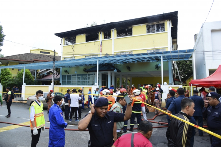 Police and rescue personnel work at an Islamic religious school cordoned off after a fire on the outskirts of Kuala Lumpur Thursday, Sept. 14, 2017. A fire department official in Malaysia said a fire at the Islamic religious school has killed people, mostly teenagers. (AP Photo)