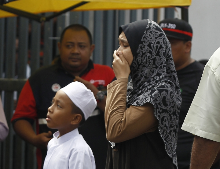 Unidentified Muslim cry outside an Islamic religious school following a fire on the outskirts of Kuala Lumpur Thursday, Sept. 14, 2017. The official said the fire, which killed people, mostly teenagers, started early Thursday at the top floor of the three-story building. (AP Photo/Daniel Chan)