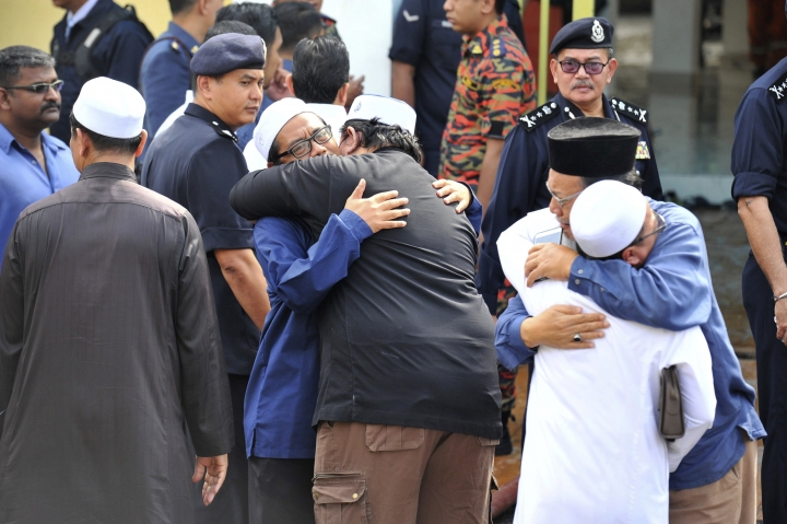 Unidentified Muslim hug each other outside an Islamic religious school following a fire on the outskirts of Kuala Lumpur Thursday, Sept. 14, 2017. The official said the fire, which killed people, mostly teenagers, started early Thursday at the top floor of the three-story building. (AP Photo)