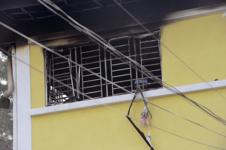 Forensic police officer investigates an Islamic religious school following a fire on the outskirts of Kuala Lumpur Thursday, Sept. 14, 2017. The official said the fire, which killed people, mostly teenagers, started early Thursday at the top floor of the three-story building. (AP Photo)