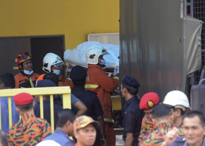 Bodies are carries out by rescue personnel from an Islamic religious school after firefighters put out a fire on the outskirts of Kuala Lumpur Thursday, Sept. 14, 2017. The official said the fire, which killed people, mostly teenagers, started early Thursday at the top floor of the three-story building. (AP Photo)