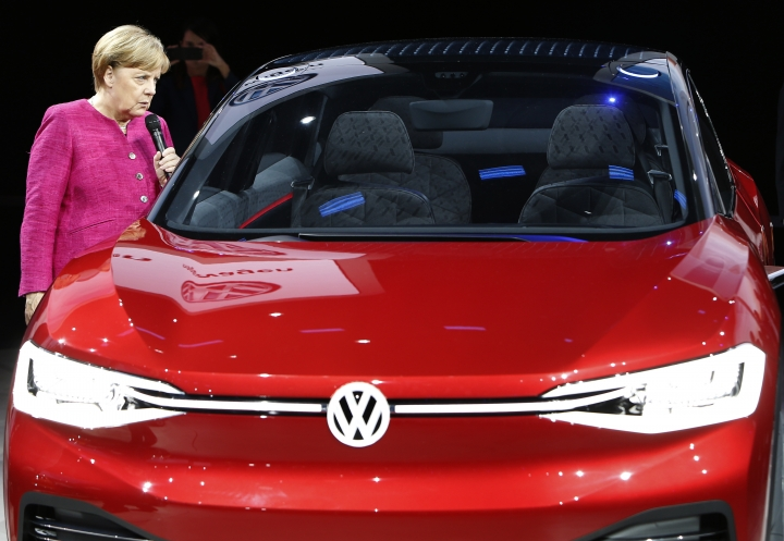 A woman takes a picture of German Chancellor Angela Merkel, left, at the booth of the German car manufacturer Volkswagen during Merkel's visit at the Frankfurt Auto Show IAA in Frankfurt, Germany, Thursday, Sept. 14, 2017. (AP Photo/Michael Probst)