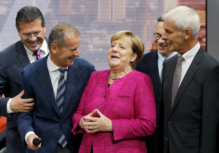 German Chancellor Angela Merkel, center, smiles together with VW group CEO Matthias Mueller, right, and VW Cars CEO Herbert Diess, 2nd left, as she arrives at the booth of the German car manufacturer Volkswagen during her visit at the Frankfurt Auto Show IAA in Frankfurt, Germany, Thursday, Sept. 14, 2017. (AP Photo/Michael Probst)