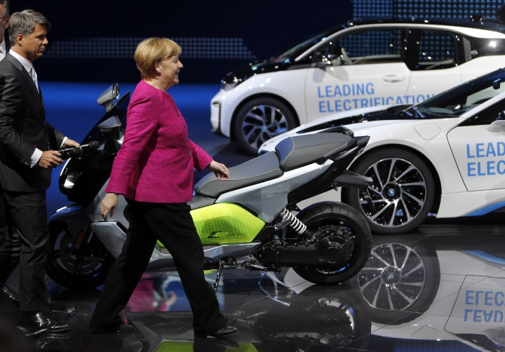 German Chancellor Angela Merkel, right, and the CEO of BMW, Harald Krueger, left, arrive at the booth of the German car manufacturer BMW during Merkel's visit at the Frankfurt Auto Show IAA in Frankfurt, Germany, Thursday, Sept. 14, 2017. (AP Photo/Michael Probst)