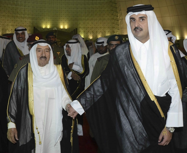 FILE- In this June 7, 2017 file photo, released by Kuwait News Agency, KUNA, Kuwait's Emir Sheikh Sabah Al Ahmad Al Sabah, left, holds the hand of Qatar's Emir Sheikh Tamim bin Hamad Al Thani in Doha, Qatar. Qatar likely faces a deadline this weekend to comply with a list of demands issued to it by Arab nations that have cut diplomatic ties to the energy-rich country, though its leaders already have dismissed the ultimatum. (KUNA via AP, File)