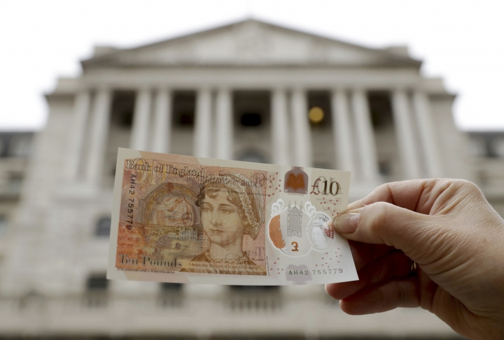 One of the new British 10 pound notes is posed for photographs outside the Bank of England in the City of London, Thursday, Sept. 14, 2017. The new polymer note, released for circulation on Thursday, features the renowned novelist Jane Austen and is the first UK banknote with a tactile feature to support blind and partially sighted users. (AP Photo/Matt Dunham)
