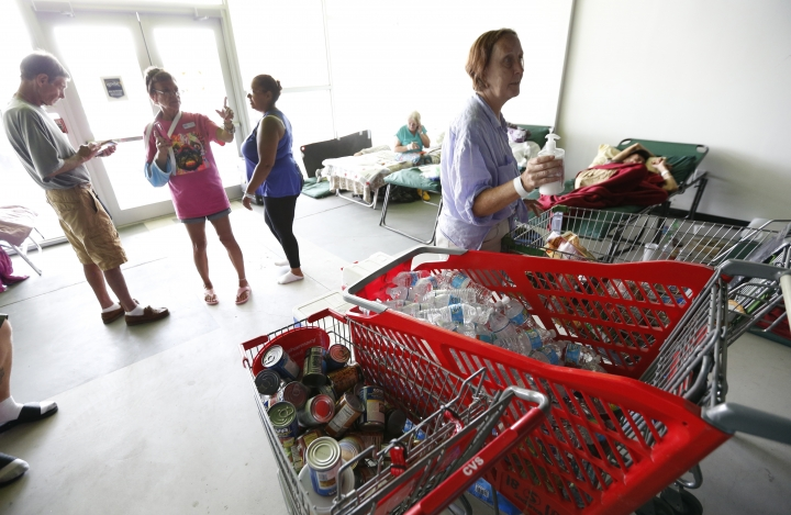 Shopping carts full of caned food and water are shown as evacuees chat or rest at a special needs shelter, Thursday, Sept. 14, 2017, at Florida International University in Miami, Fla. About 30 people, including staff with the Florida Keys Outreach Coalition for the Homeless from Key West, Fla., were sheltered in a storefront underneath a parking garage on campus. (AP Photo/Wilfredo Lee)