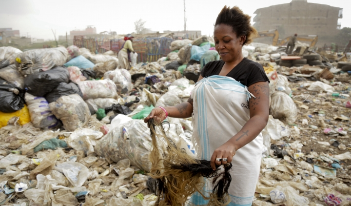 In this photo taken Wednesday, Aug. 23, 2017, Winnie Wanjira, 31, separates hair pieces she bought from a man who collects them from the piles of rubbish, at the Dandora municipal dumpsite in Nairobi, Kenya. In one of Africa's largest dumps, some residents are making a living by collecting and recycling hair from the mountains of rubbish. (AP Photo/Adelle Kalakouti)