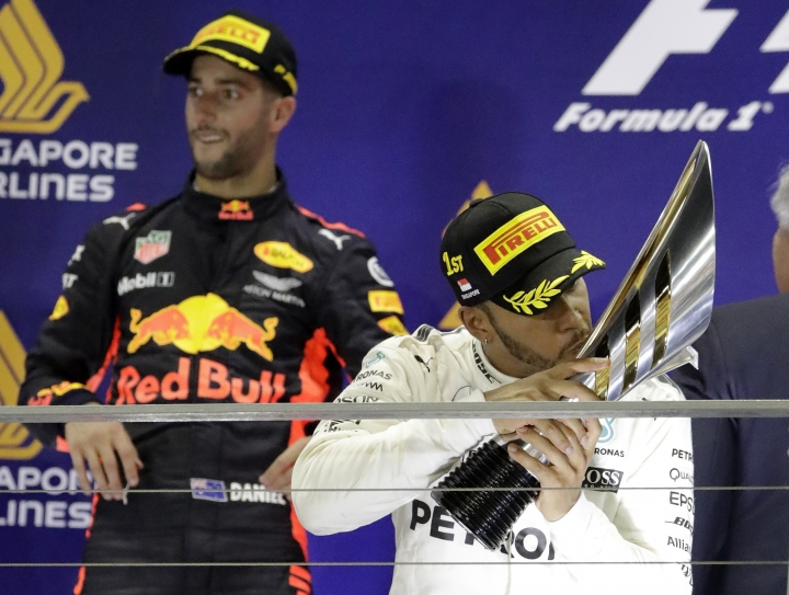 Mercedes driver Lewis Hamilton, right, of Britain kisses his trophy after winning the Singapore Formula One Grand Prix on the Marina Bay City Circuit Singapore, Sunday, Sept. 17, 2017. Red Bull driver Daniel Ricciardo of Australia looks on after his second place finish. (AP Photo/Wong Maye-E)