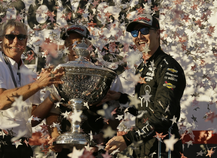 Josef Newgarden, right, stands and celebrates after being presented the Astor Cup for winning the IndyCar championship Sunday, Sept. 17, 2017, in Sonoma, Calif. Looking on at center is team owner Roger Penske. (AP Photo/Eric Risberg)