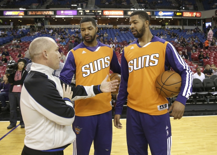 FILE - In this Oct. 17, 2013, file photo, official Ron Garretson talks with Phoenix Suns forwards Marcus Morris center and his twin brother, Markieff, before the Suns' NBA preseason basketball game against the Sacramento Kings in Sacramento, Calif. Opening statements will begin Monday, Sept. 18, 2017, for the trial of the twins, who allegedly assaulted a man outside a Phoenix recreation center two years ago. (AP Photo/Rich Pedroncelli, File)