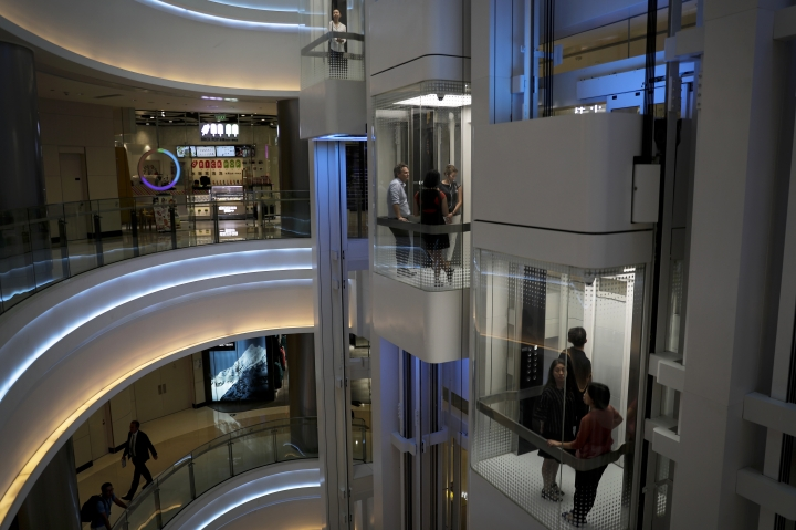 People take elevators at a newly opened up-scale shopping mall in Beijing, Tuesday, Sept. 19, 2017. A foreign business group appealed to China on Tuesday to move faster in carrying out promises to open its state-dominated economy and warned that inaction might fuel a backlash against free trade. Beijing faces mounting complaints from Washington and Europe about barriers in industries from finance to medical equipment while its own competitors have largely unfettered access to foreign markets. (AP Photo/Andy Wong)