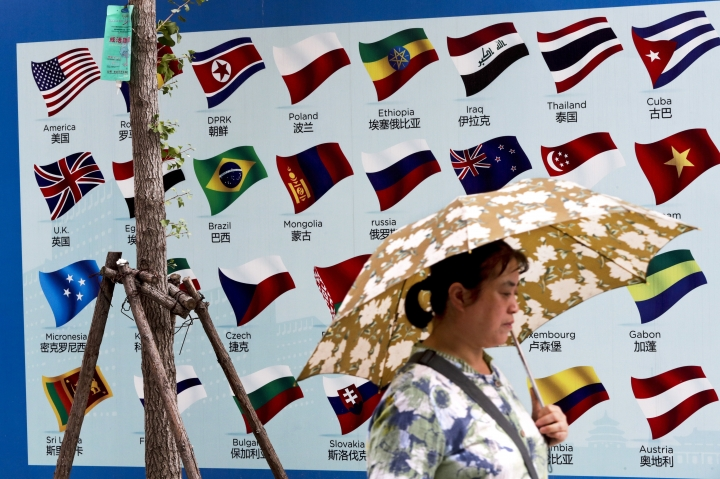 FILE - In this Sept. 4, 2017, file photo, a woman carries an umbrella past a board displaying countries' national flags in Beijing. A foreign business group appealed to China on Tuesday, Sept. 19, 2017, to move faster in carrying out promises to open its state-dominated economy and warned that inaction might fuel a backlash against free trade. Beijing faces mounting complaints from Washington and Europe about barriers in industries from finance to medical equipment while its own competitors have largely unfettered access to foreign markets. (AP Photo/Andy Wong, File)