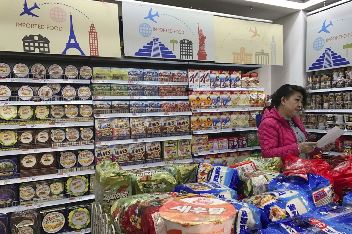 FILE - In this March 17, 2017, file photo, a vendor takes stock of imported food at a mall in Beijing. A foreign business group appealed to China on Tuesday, Sept. 19, 2017, to move faster in carrying out promises to open its state-dominated economy and warned that inaction might fuel a backlash against free trade. Beijing faces mounting complaints from Washington and Europe about barriers in industries from finance to medical equipment while its own competitors have largely unfettered access to foreign markets. (AP Photo/Ng Han Guan, File)