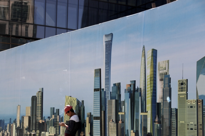 A worker smokes while checking on his mobile phone at a construction site wall depicting the skyscrapers in the Chinese capital at the Central Business District in Beijing, Tuesday, Sept. 19, 2017. A foreign business group appealed to China on Tuesday to move faster in carrying out promises to open its state-dominated economy and warned that inaction might fuel a backlash against free trade. Beijing faces mounting complaints from Washington and Europe about barriers in industries from finance to medical equipment while its own competitors have largely unfettered access to foreign markets. (AP Photo/Andy Wong)