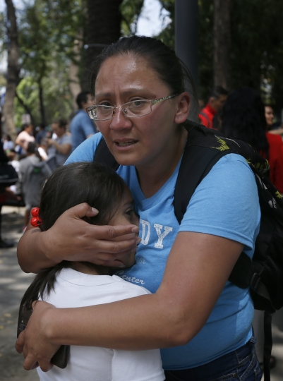 A woman hugs a child outside a school in the Roma Norte neighborhood of Mexico City, after an earthquake in Mexico, Tuesday Sept. 19, 2017. Throughout Mexico City, rescuer workers and residents dug through the rubble of collapsed buildings seeking survivors following a 7.1 magnitude quake. (AP Photo/Marco Ugarte)