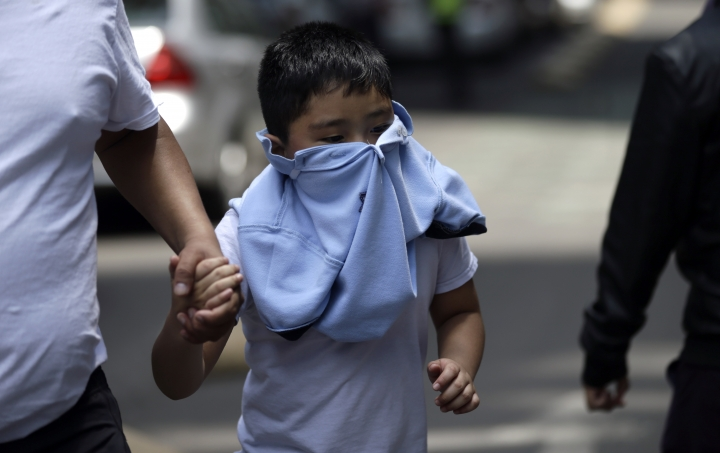 A boy with his face covered due to a gas leak holds aman's hand as people gather in Reforma Avenue after an earthquake in Mexico City, Tuesday Sept. 19, 2017. A powerful earthquake jolted central Mexico on Tuesday, causing buildings to sway sickeningly in the capital on the anniversary of a 1985 quake that did major damage.(AP Photo/Marco Ugarte)