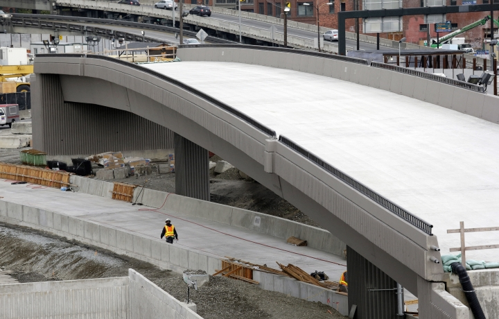 In this photo taken Tuesday, Sept. 19, 2017, a worker walks under a portion of a new offramp for Highway 99 where a tunnel for the roadway is still being constructed in Seattle. The offramp has a new type of column that flexes when the ground shakes in an earthquake, then snaps back to its original position so that the structure not only survives a quake without collapsing but also sustains so little damage that it can be used immediately. Funded by the California Department of Transportation, scientists at a Nevada seismology lab plan to test a combination of new bridge designs on a giant ''shake table'' to see if they can better withstand big earthquakes like the one that hit Mexico on Tuesday. (AP Photo/Elaine Thompson)