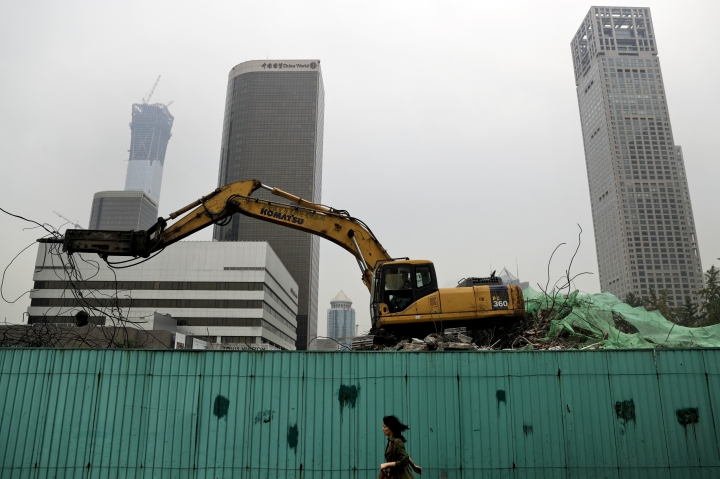 In this photo taken on Friday, Sept. 15, 2017, a woman walks by a machine demolish an old building at the Central Business District in Beijing. The Standard & Poor's rating agency cut China's credit rating on Thursday, Sept. 21, 2017 due to its rising debts, highlighting challenges faced by Communist leaders as they cope with slowing economic growth. (AP Photo/Andy Wong)