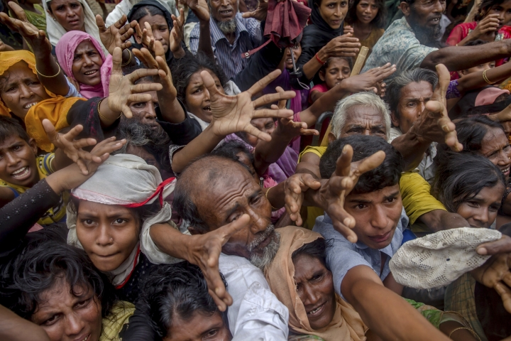 Rohingya Muslims, who crossed over from Myanmar into Bangladesh, stretch their arms out to collect rice bags distributed by aid workers near Balukhali refugee camp, Bangladesh, Friday, Sept. 22, 2017. More than 420,000 Rohingya refugees have fled from Myanmar to Bangladesh in less than a month, with most ending up in camps in the Bangladeshi district of Cox's Bazar, which already had hundreds of thousands of Rohingya refugees who had fled prior rounds of violence in Myanmar. (AP Photo/Dar Yasin)