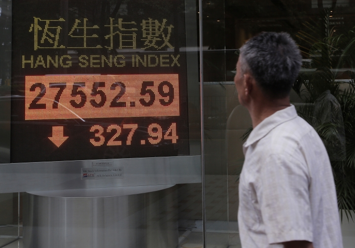 A man watches an electronic board showing Hong Kong share index outside a local bank in Hong Kong, Monday, Sept. 25, 2017. Asian shares were mixed on Monday as investors turned their attention to global politics and evaluated weekend election results from Germany and New Zealand. (AP Photo/Vincent Yu)
