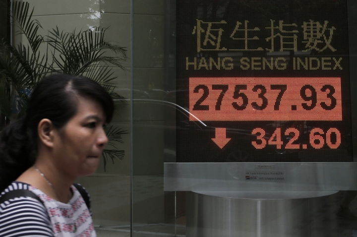 A woman walks past an electronic board showing Hong Kong share index outside a local bank in Hong Kong, Monday, Sept. 25, 2017. Asian shares were mixed on Monday as investors turned their attention to global politics and evaluated weekend election results from Germany and New Zealand. (AP Photo/Vincent Yu)