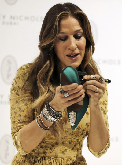 "FILE - In this Dec. 7, 2014 file photo, actress and designer Sarah Jessica Parker, signs a shoe during the SJP shoe collection signing ceremony in Dubai, United Arab Emirates. Parker of ""Sex and the City"" fame will be taking four guests shoe-shopping at Bloomingdale's, then sending them to the New York City Ballet as part of an Airbnb launch of local tours and other experiences in New York. Parker's listing goes live Tuesday, with four spots at $400 each, first come first served. The money will benefit the New York City Ballet, where Parker is a board member. (AP Photo/Kamran Jebreili, File)"