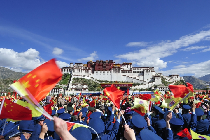 FILE - In this Tuesday, Sept. 8, 2015 file photo, people wave Chinese flags during a ceremony marking the 50th anniversary of the founding of the Tibet Autonomous Region at the square of the Potala Palace in Lhasa, capital of southwestern China's Tibet Autonomous Region. Visits by foreigners to the sometimes volatile Himalayan region of Tibet will be suspended until the end of a major Chinese political meeting in Beijing next month, a tour operator said on Monday, Sept. 25, 2017. (Chinatopix Via AP, File)