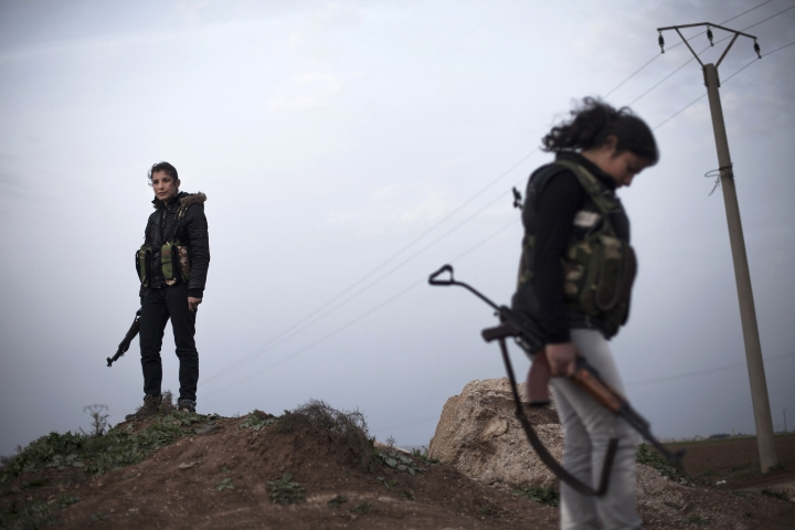 FILE - In thisMarch. 3, 2013 file photo, Kurdish female members of the Popular Protection Units stand guard at a check point near the northeastern city of Qamishli, Syria. The Monday, Sept. 25, 2017, Kurdish independence referendum in Iraq is the latest in a series ofmoves toward formal secession or de facto fragmentation caused by conflict, race or religion in the Middle East. It's a trend viewed with considerable alarm in a region that had seriously flirted with merging its nations in post-colonial years more than a half century ago. (AP Photo/Manu Brabo, File)
