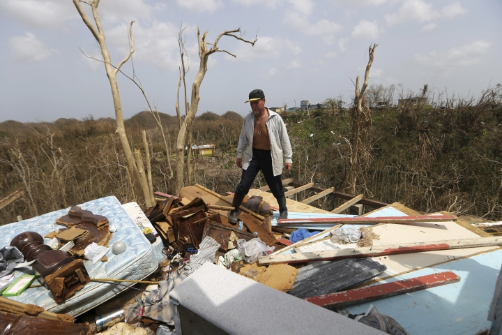 Jose Trinidad walks on what's left of his home in Montebello, Puerto Rico in the aftermath of Hurricane Maria, Tuesday, Sept. 26, 2017. Five days after the Category 4 storm slammed into Puerto Rico, many of the more than 3.4 million U.S. citizens in the territory were still without adequate food, water and fuel. Flights off the island were infrequent, communications were spotty and roads were clogged with debris. Officials said electrical power may not be fully restored for more than a month. (AP Photo/Gerald Herbert)