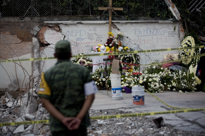 A solider looks at a memorial set up by people at the site of a building that collapsed in last week's 7.1 magnitude earthquake, at the corner of Division del Norte and Peten streets in the Santa Cruz Atoyac neighborhood of Mexico City, Tuesday, Sept. 26, 2017. Authorities pledged a return to normality, but many streets in the capital were still blocked by construction equipment and recovery teams looking to extract the last remaining bodies from the rubble. (AP Photo/Moises Castillo)